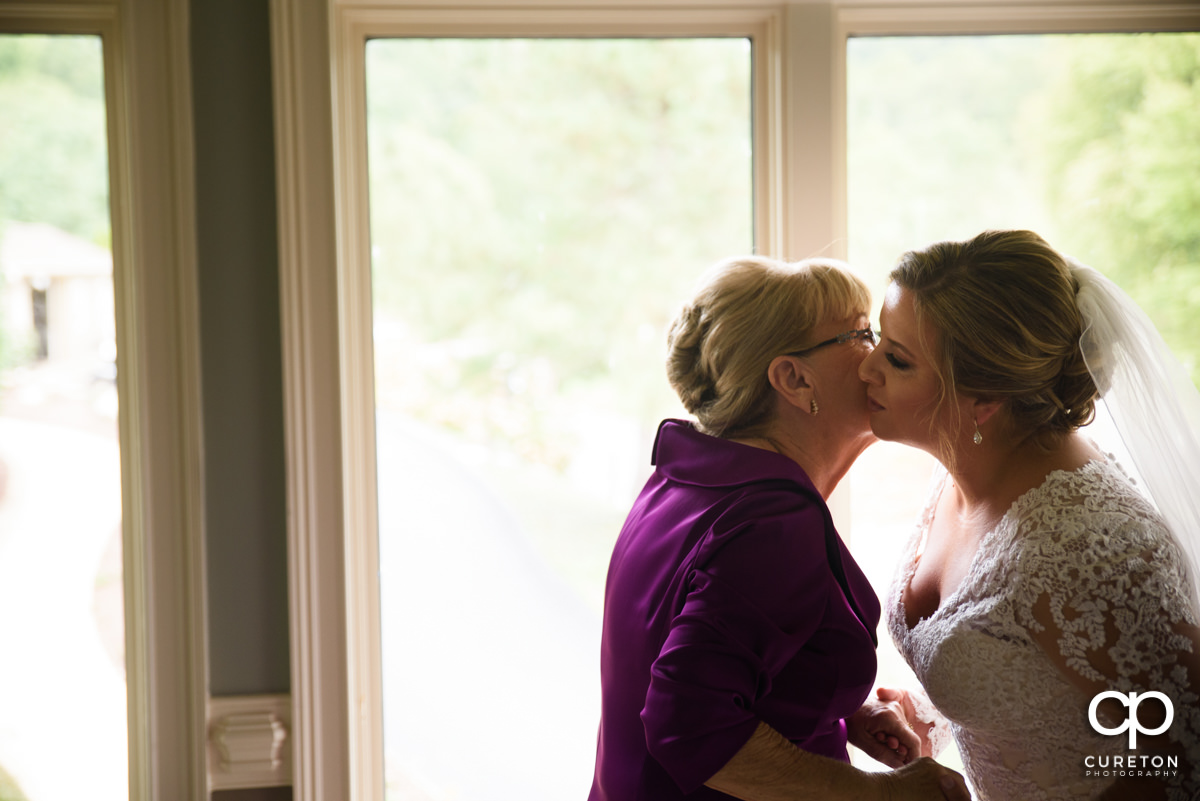 Bride's mother kissing her on the cheek.
