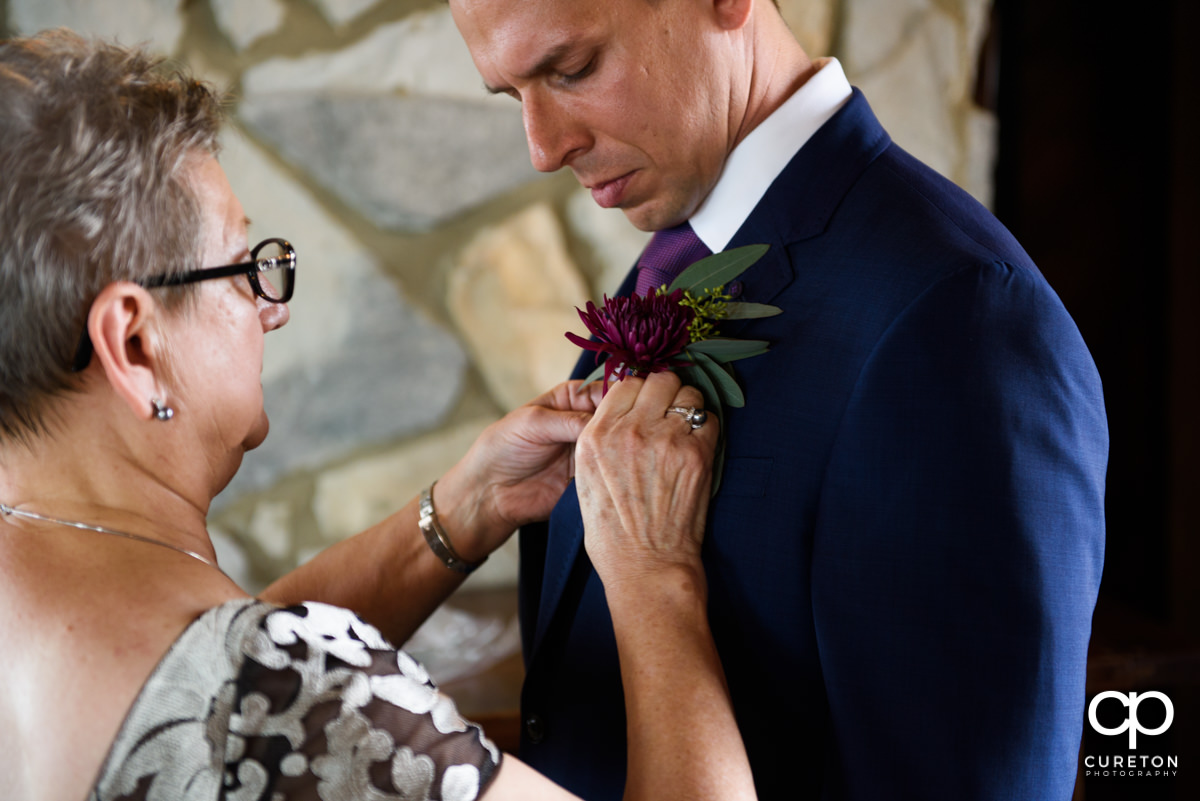 Groom's mom pinning his boutonniere on him.