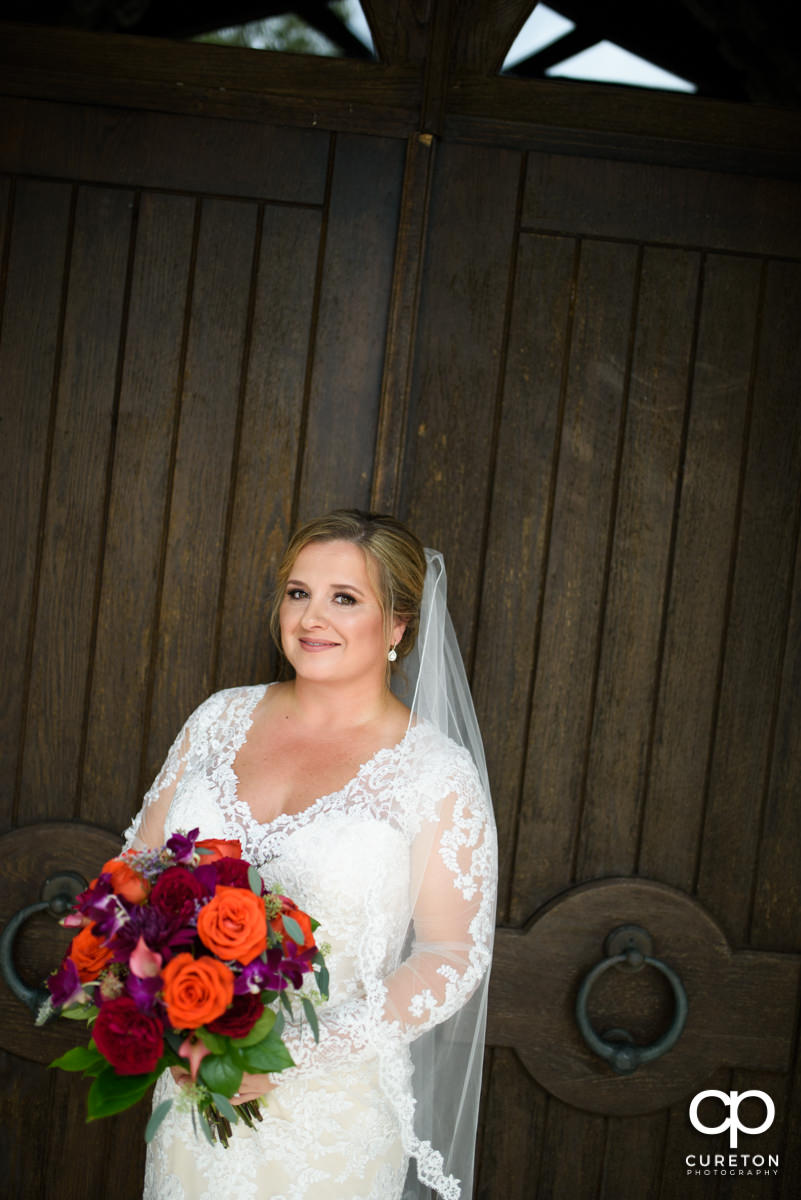 Bride in front of the double wooden doors at Glassy Chapel.