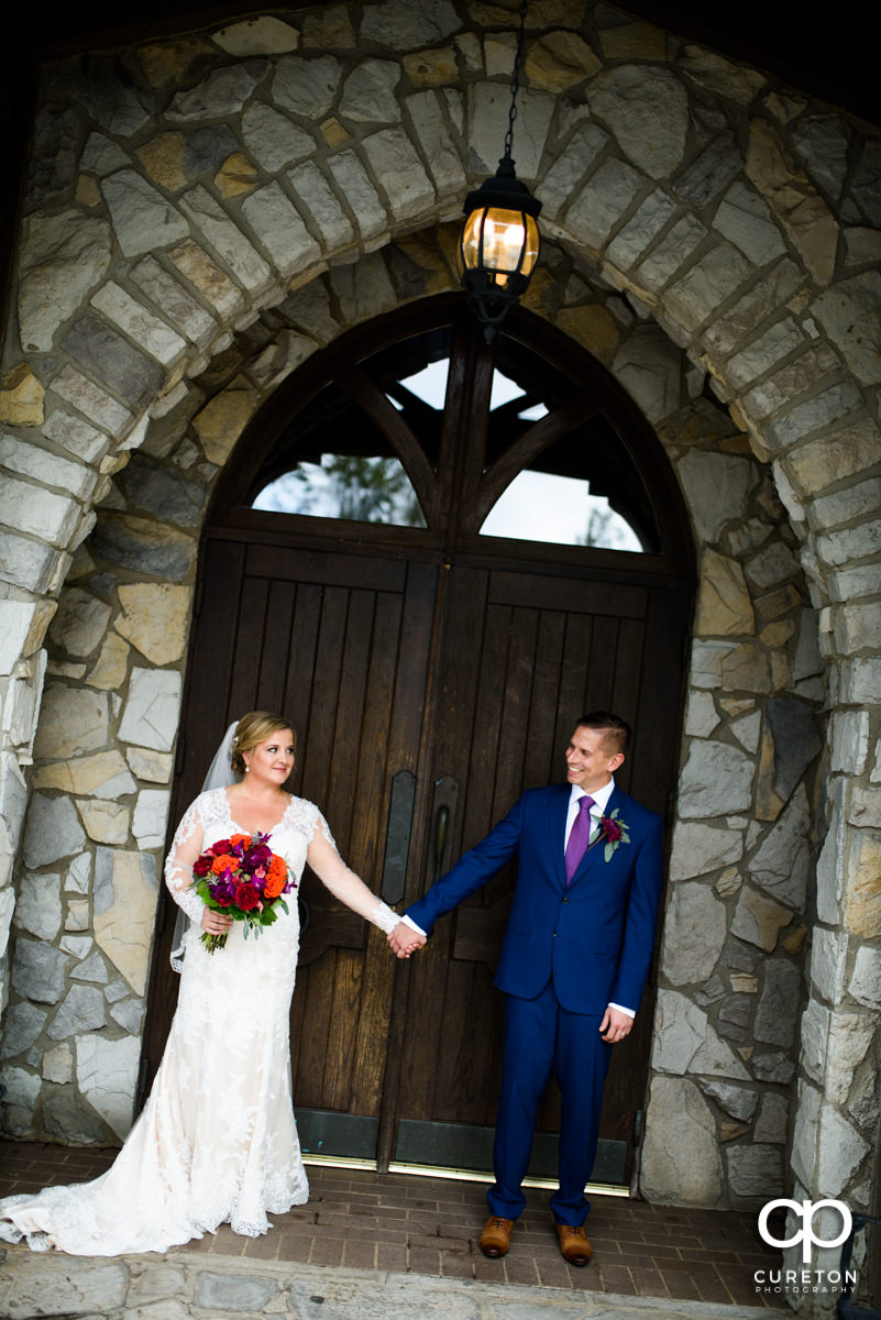 Bride and groom holding hands in front of the doors at Glassy Chapel.