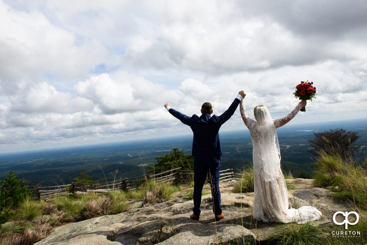 Groom and bride holding their hands in the air on the top of Glassy Chapel.