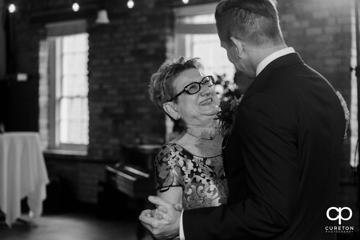 Groom's mom smiling at him during a dance at the reception.