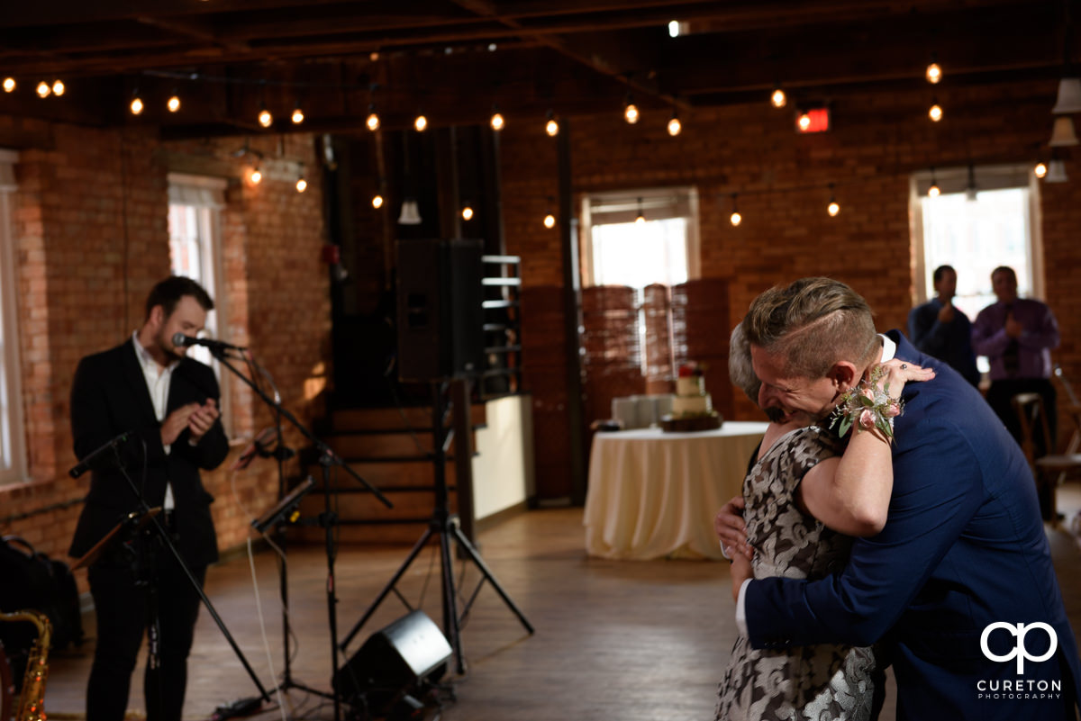 Groom hugging his mom at the reception.
