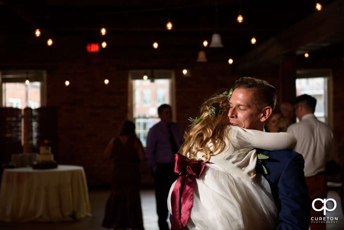 Groom dancing with the flower girl at the wedding reception.