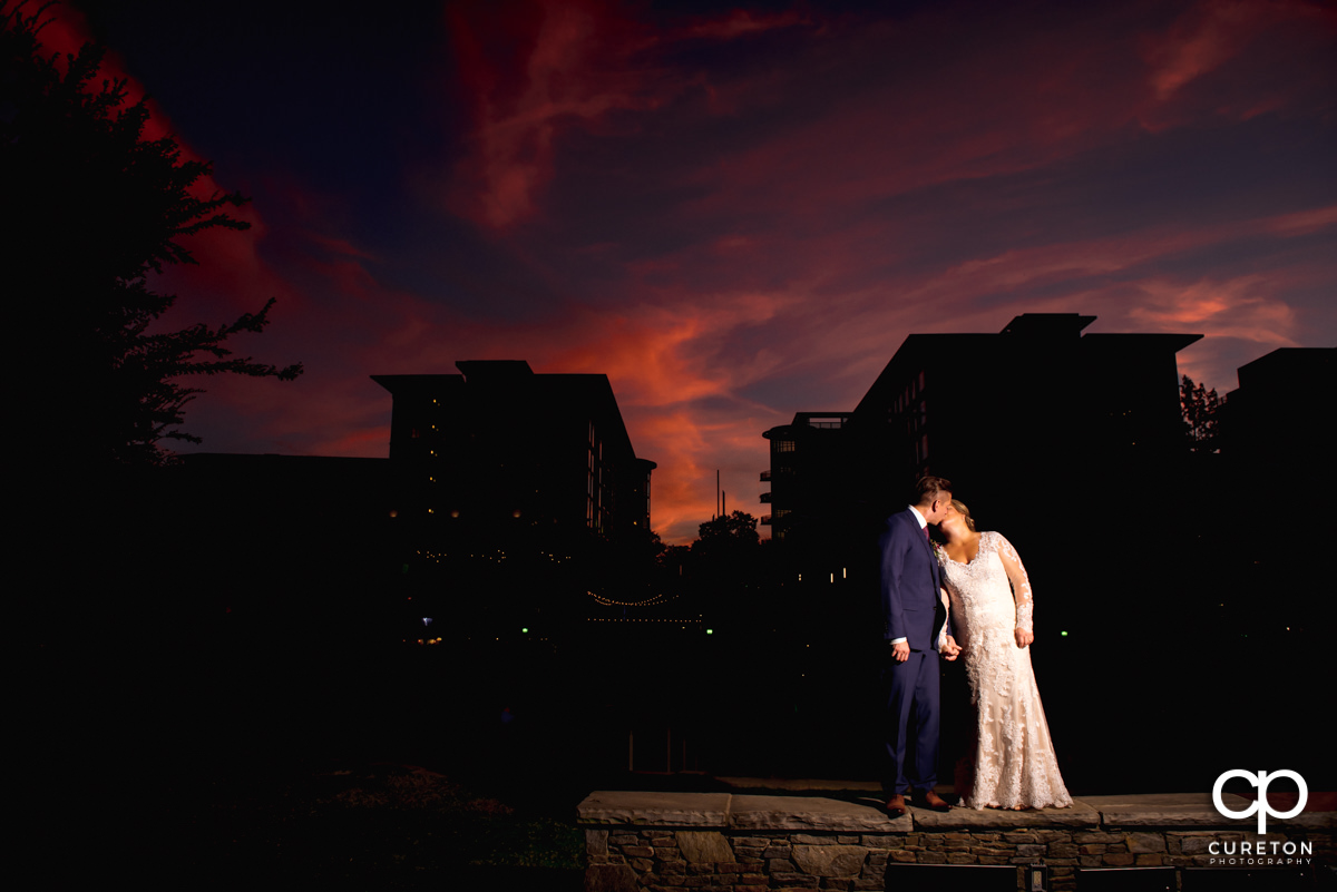 Bride and groom kissing at sunset in front of the downtown Greenville,SC skyline outside of their Larkin's Cabaret Room wedding reception.