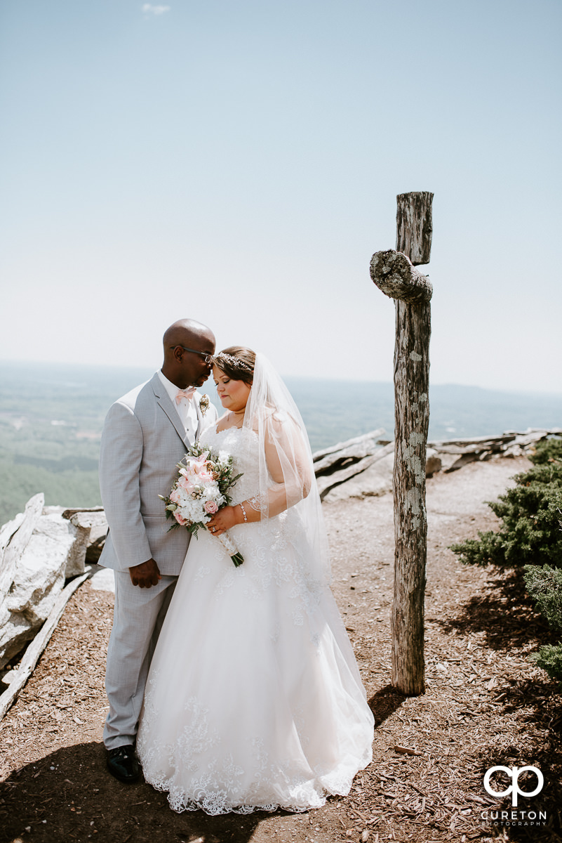 Bride and groom standing near a wooden cross on a mountain top after their wedding ceremony at the Cliffs Glassy Chapel.