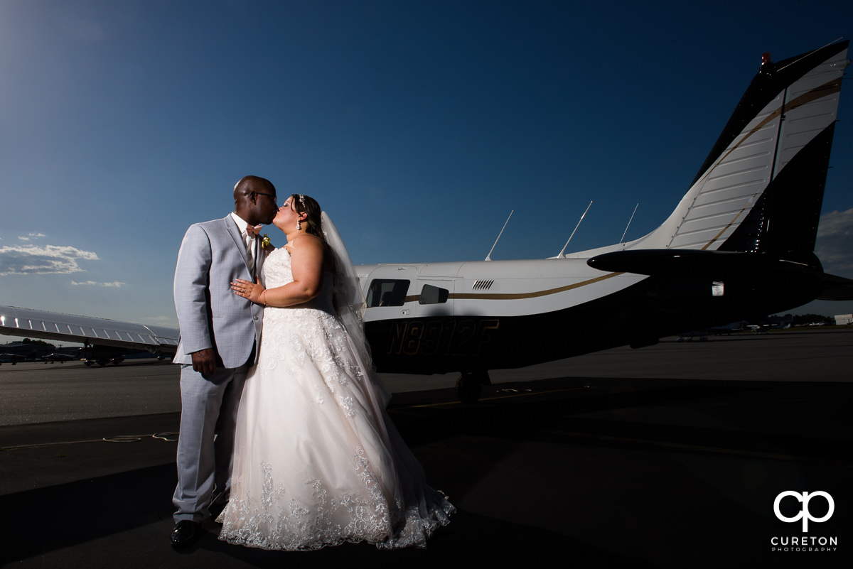 Bride and groom kissing beside an airplane at their wedding reception at the Runway Cafe Hangar in Greenville,SC.