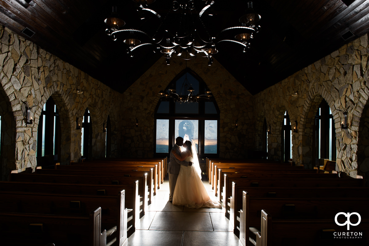 Bride and groom silhouette inside after their wedding ceremony at the Cliffs Glassy Chapel.