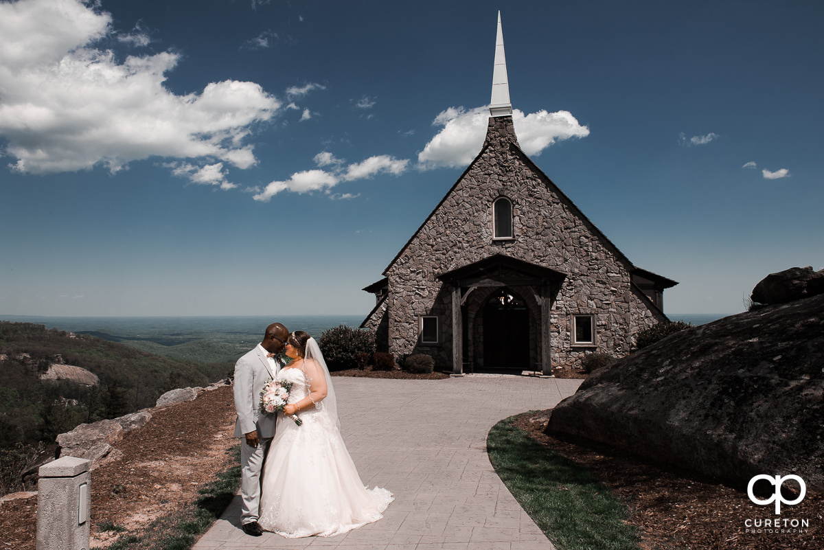 Bride and groom standing on a mountaintop after their wedding ceremony at the Cliffs Glassy Chapel.