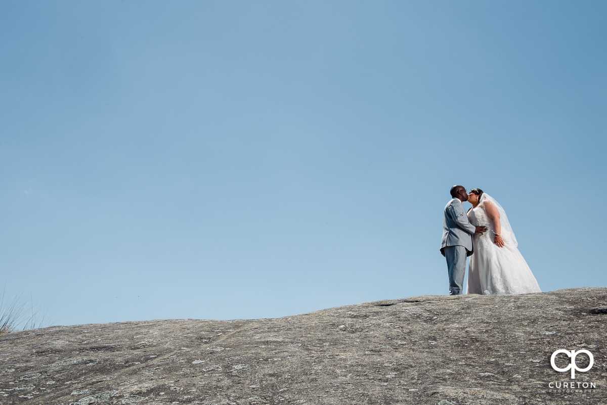 Bride and groom walking up a rock on a mountaintop at Cliffs Glassy Chapel.