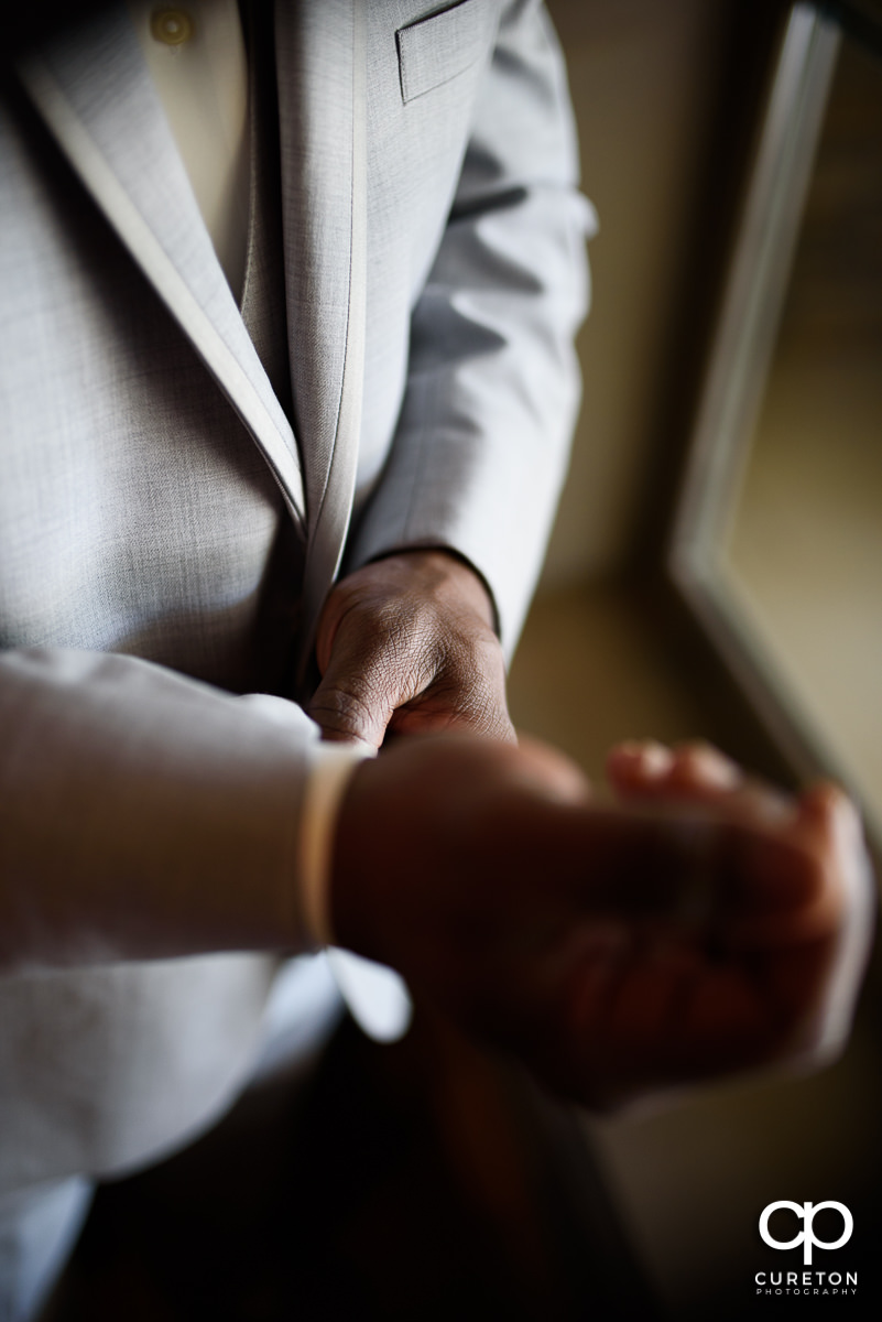 Groom adjusting his sleeves.
