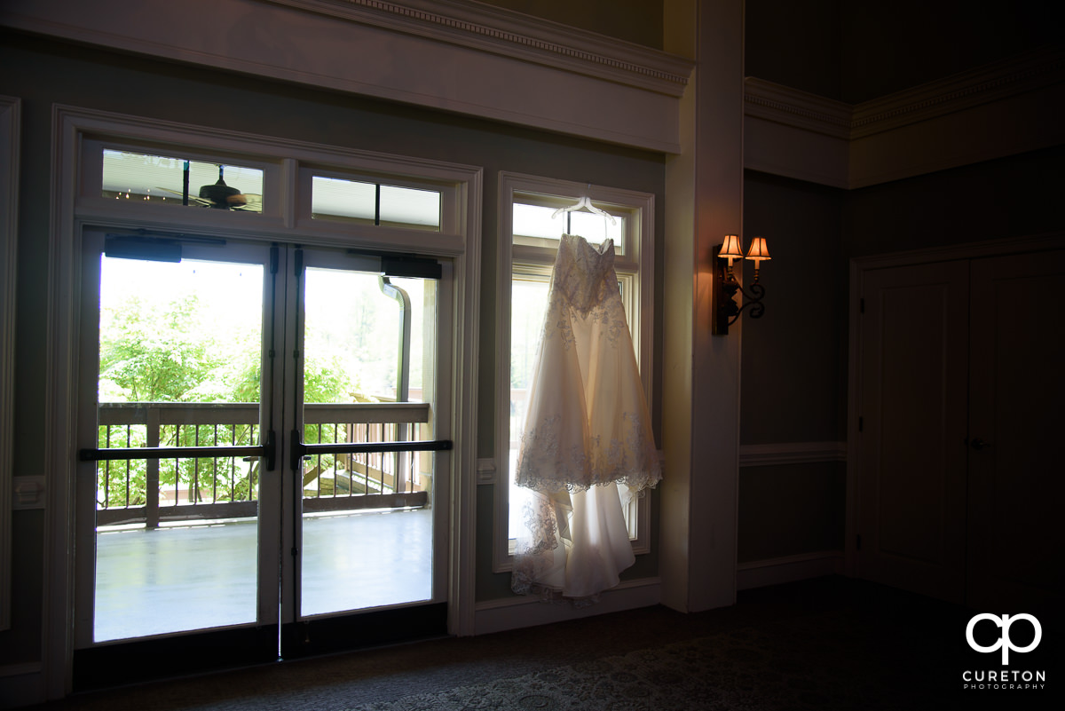 Bride's dress hanging in a window.