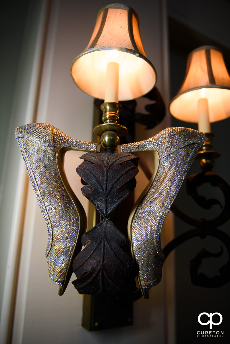 Bride's shoes hanging on a light fixture.