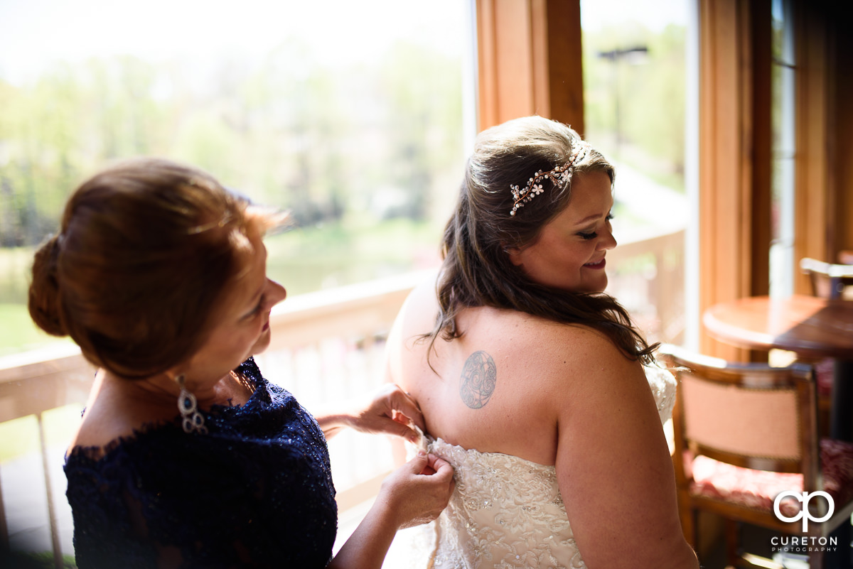 Bride putting on her dress with her mom.