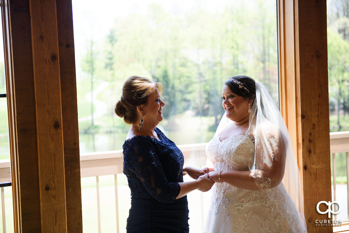 Bride and her mother standing in a window at Cliffs Glassy Clubhouse before her wedding.
