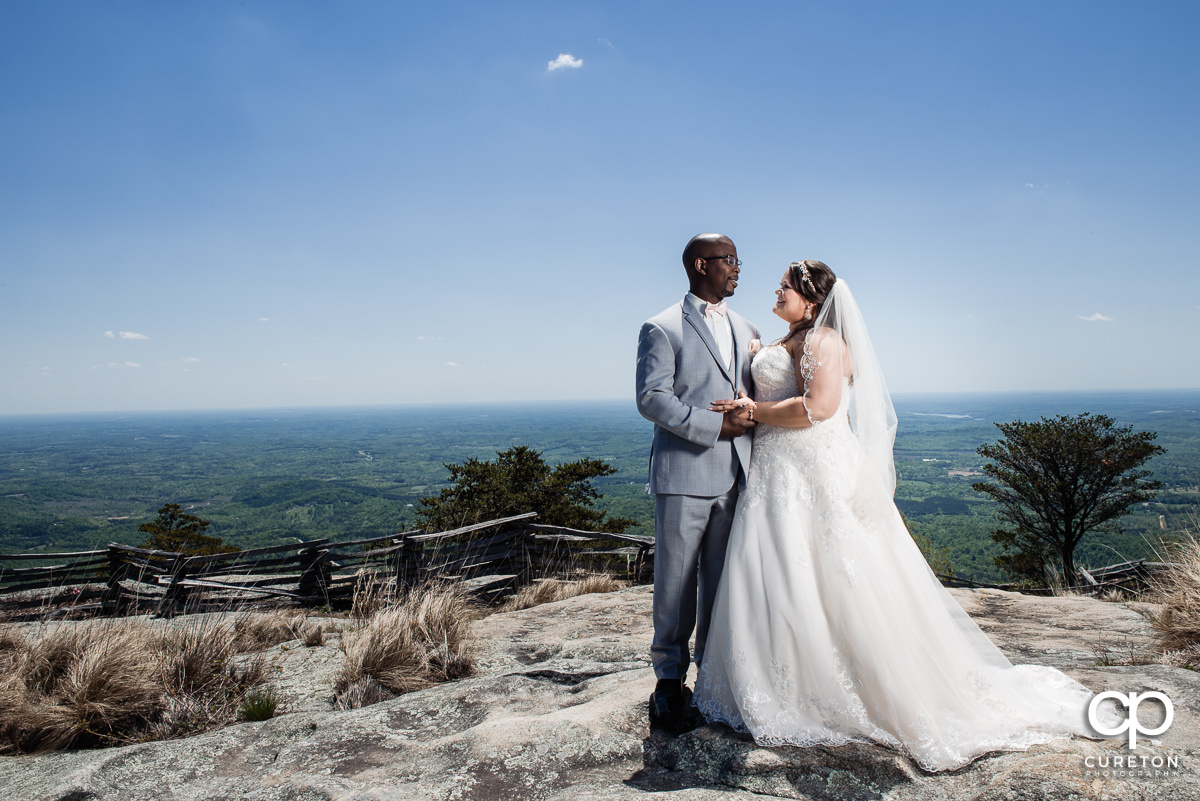Bride and groom looking at each other on a mountain top.