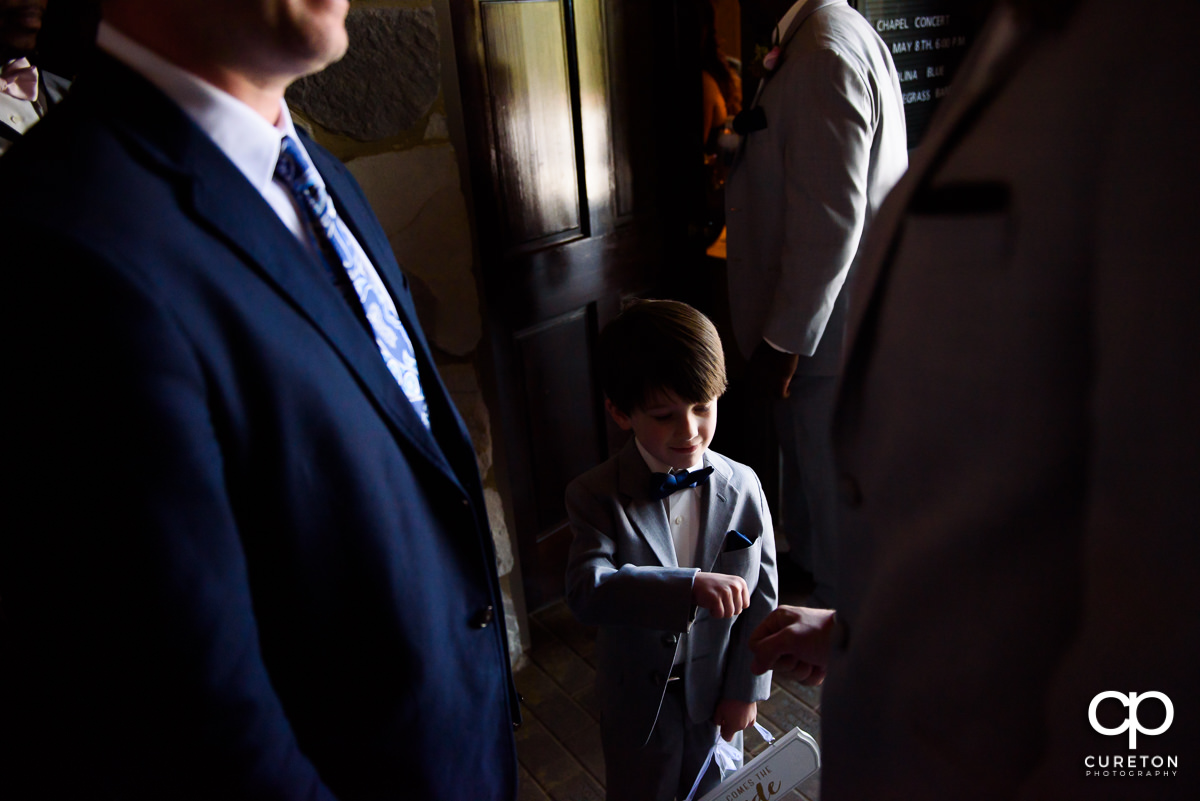 Ring bearer fist bumping a groomsmen before the wedding ceremony.