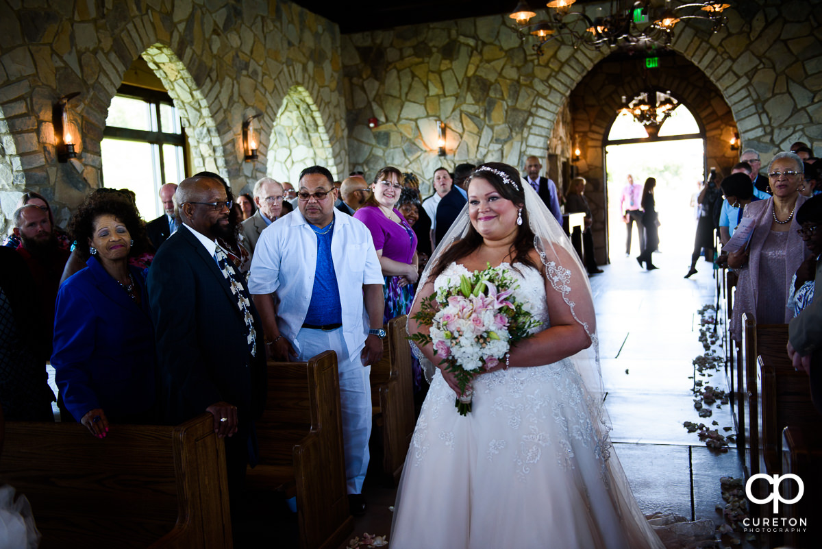 Bride walking down the aisle smiling at Glassy Chapel.