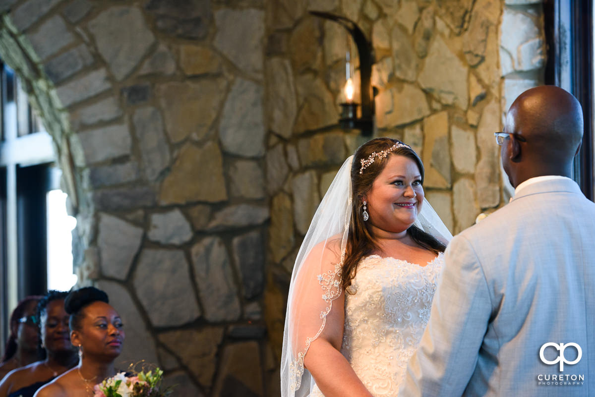 Bride smiling at her groom during the wedding ceremony at Glassy Chapel.