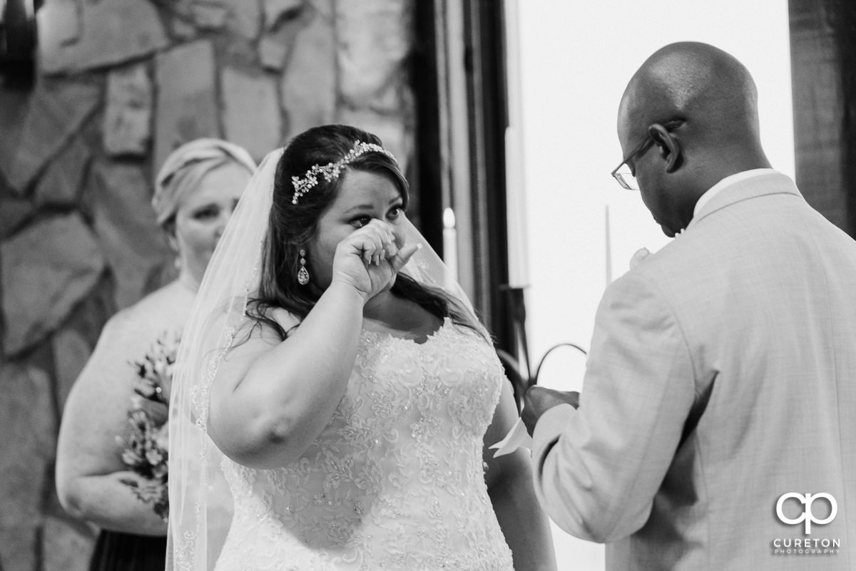 Bride wiping tears from her eyes during the wedding ceremony at Glassy Chapel.