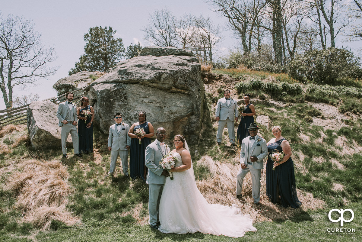 Wedding party standing by a huge rock at Glassy Chapel on a mountain top.