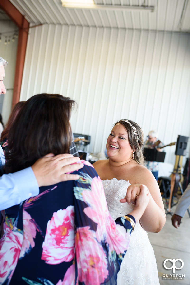 Bride laughing with guests.