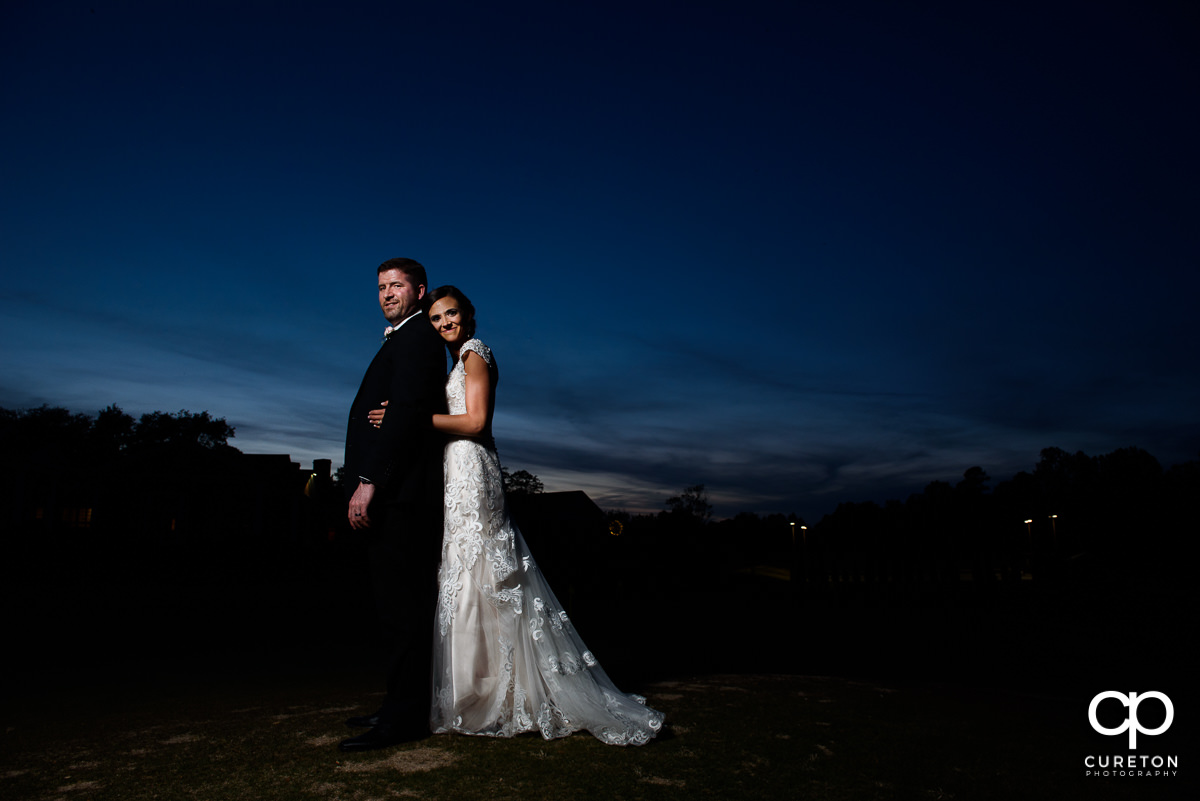 Bride holding onto her groom at sunset at their wedding reception at Green Valley Country Club.
