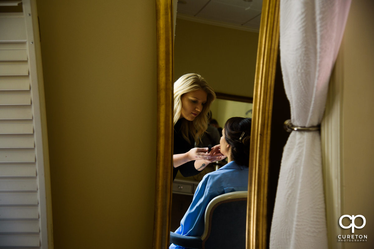 Bride getting makeup applied in the mirror.