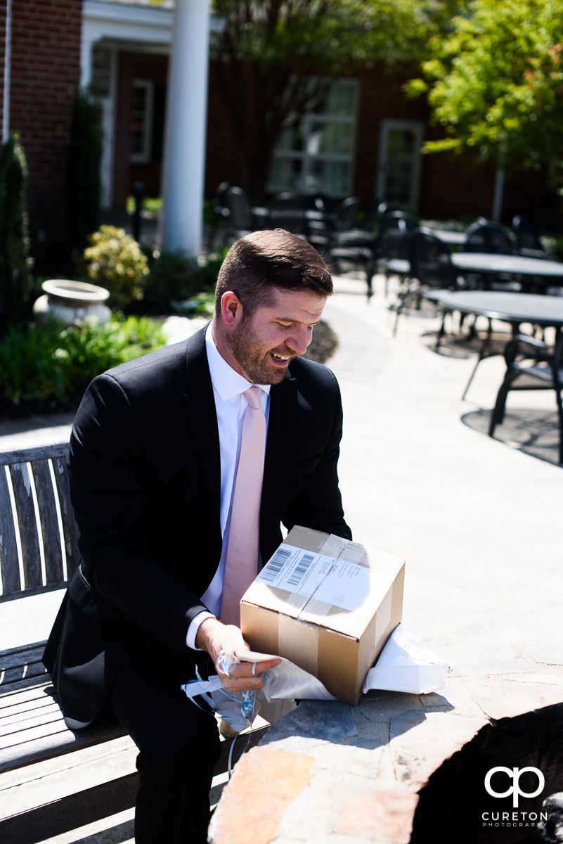 Groom opening up his gift from the bride.
