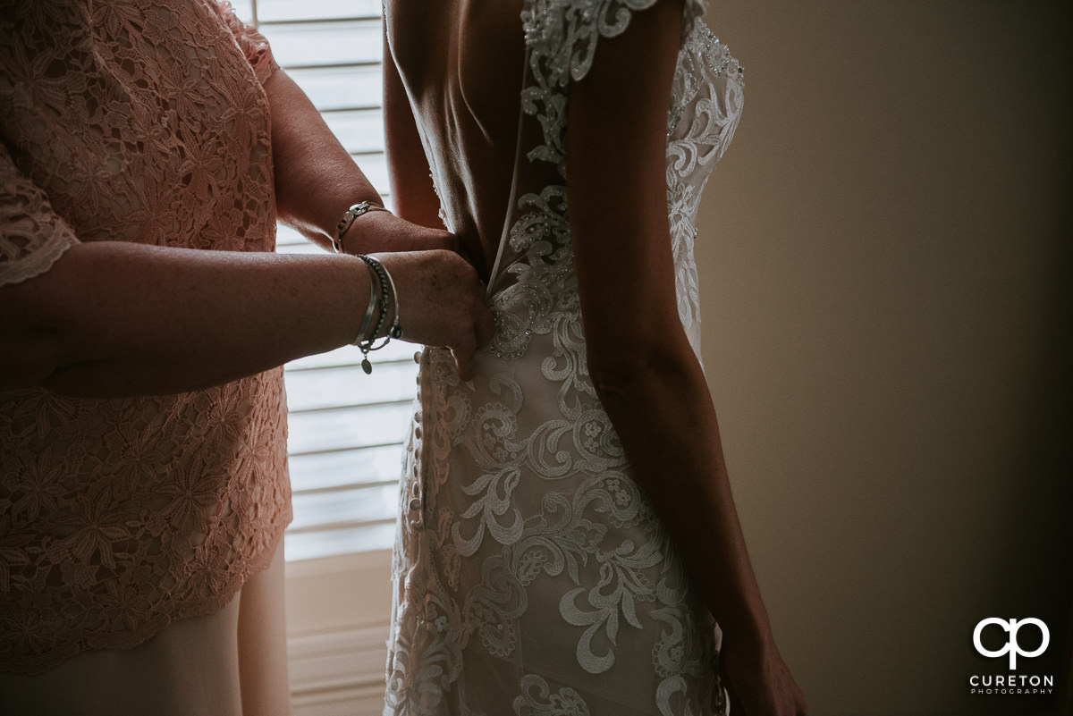 Bride's mother helping her with the back of her dress.