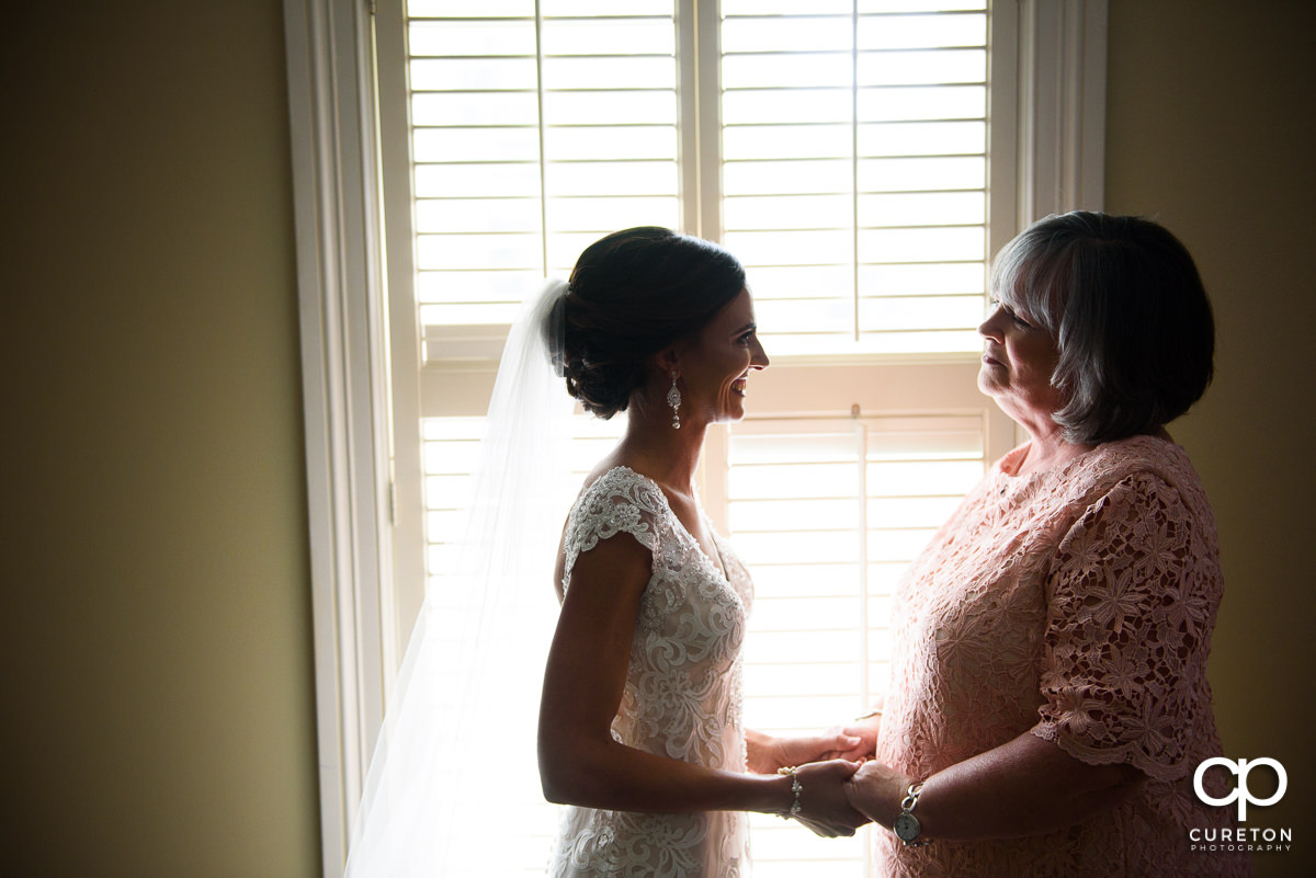 Bride holding hands with her mom before the wedding ceremony at Green Valley Country Club.