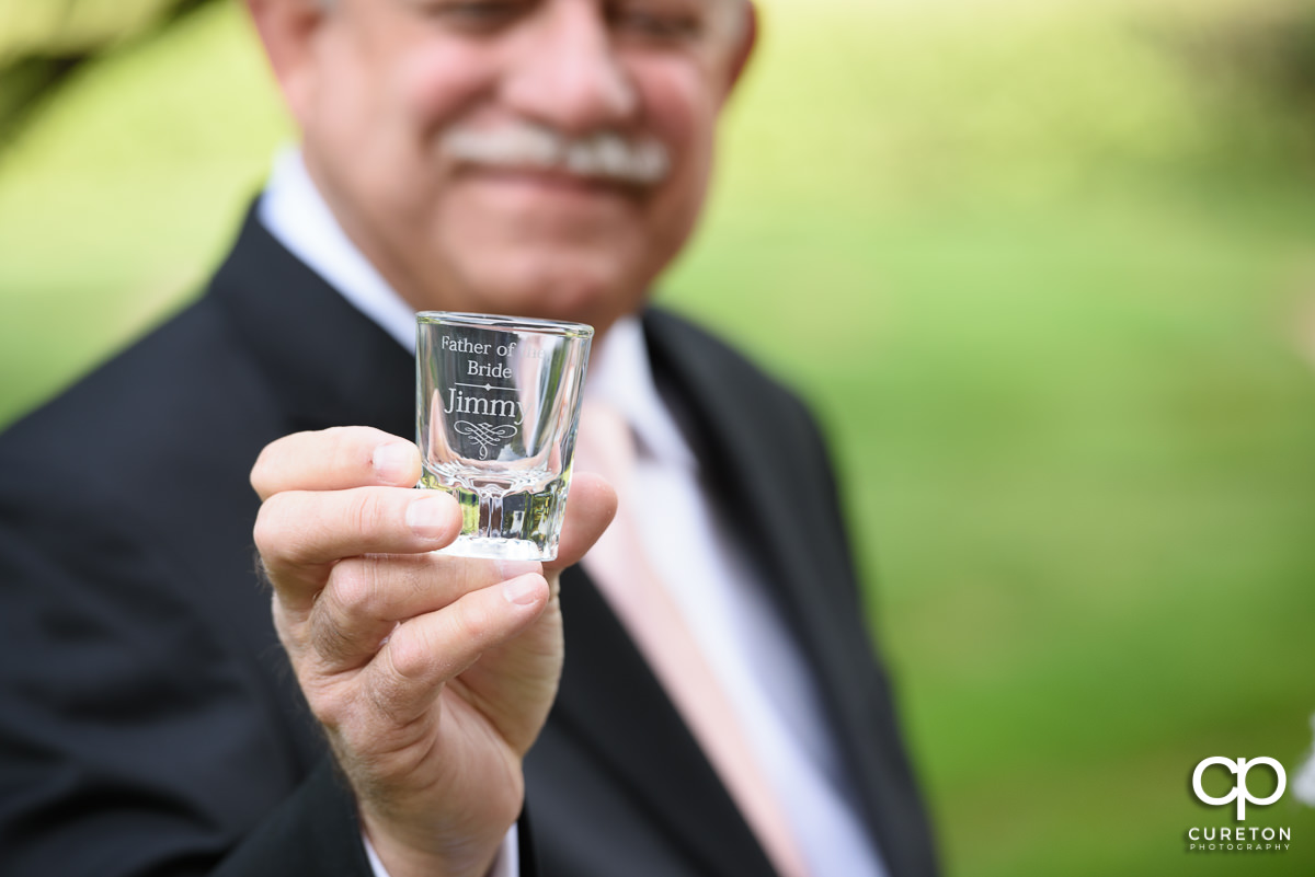 Father of the bride holding a personalized shot glass.