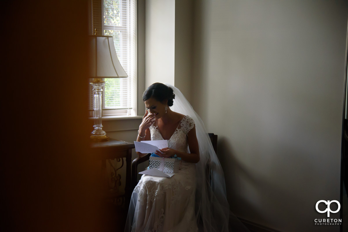 Bride tearing up while reading a letter from her groom.