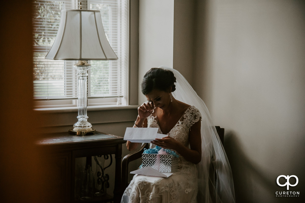 Bride tearing up while reading a letter from her groom before the wedding ceremony at Daniel Chapel.