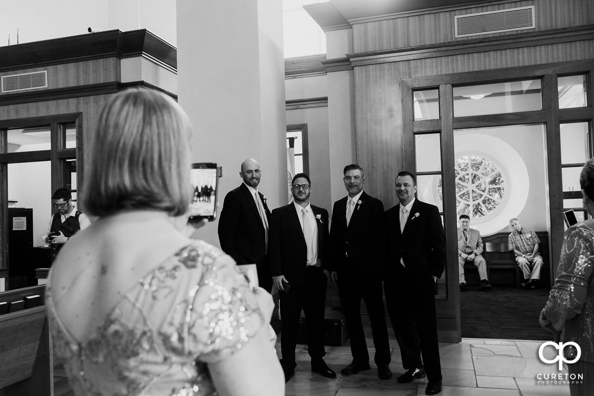 Guest taking a photo of the groomsmen.