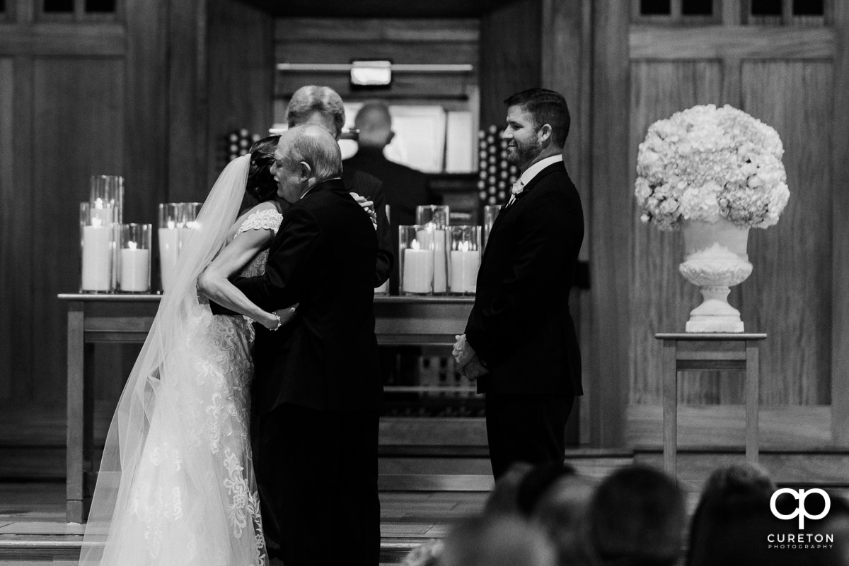 Father giving away his daughter at her wedding.