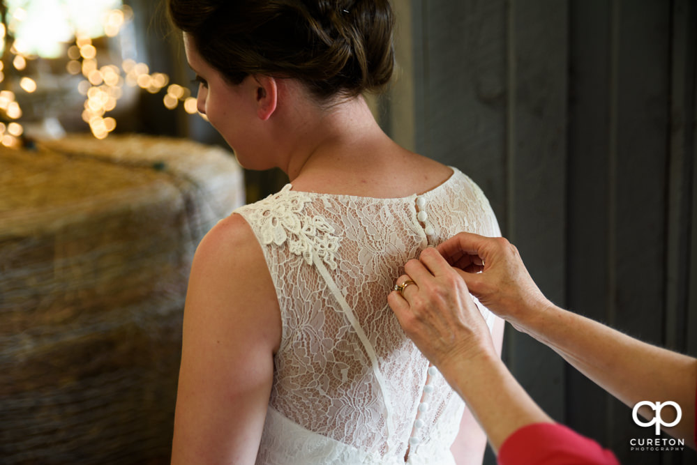 Bride's mom helping her button the dress.