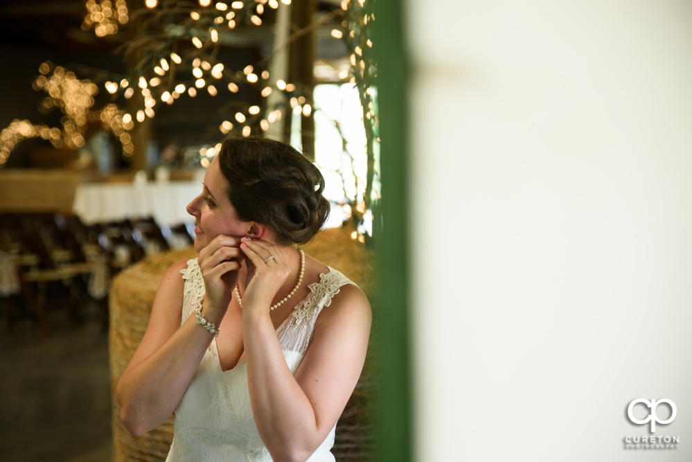Bride putting on her earrings.