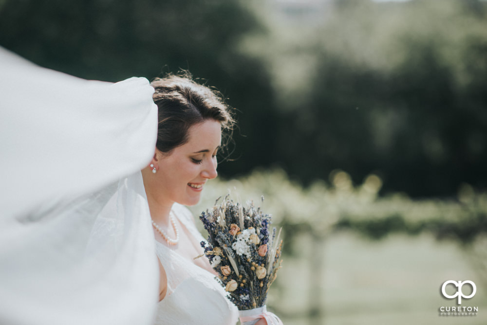 Bride with her veil blowing in the wind at Greenbrier Farms.