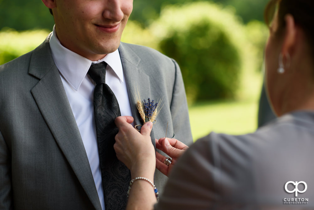 Groom getting his boutonnière pinned on.
