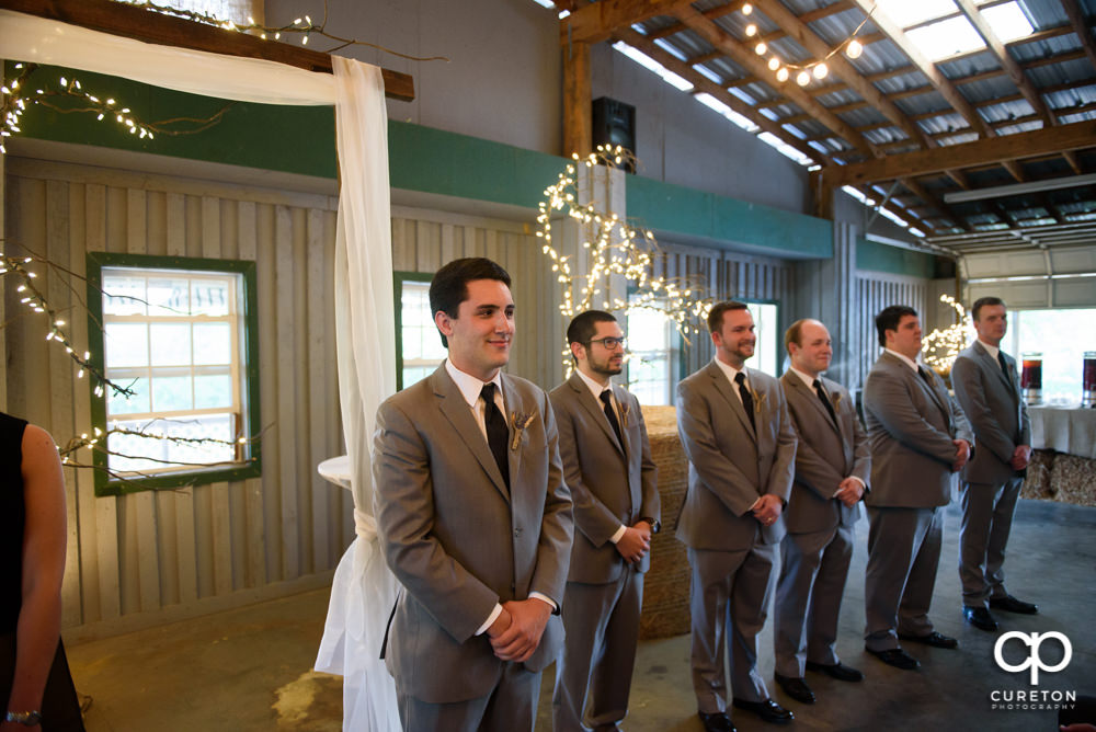 Groom sees his bride walking down the aisle for the first time.