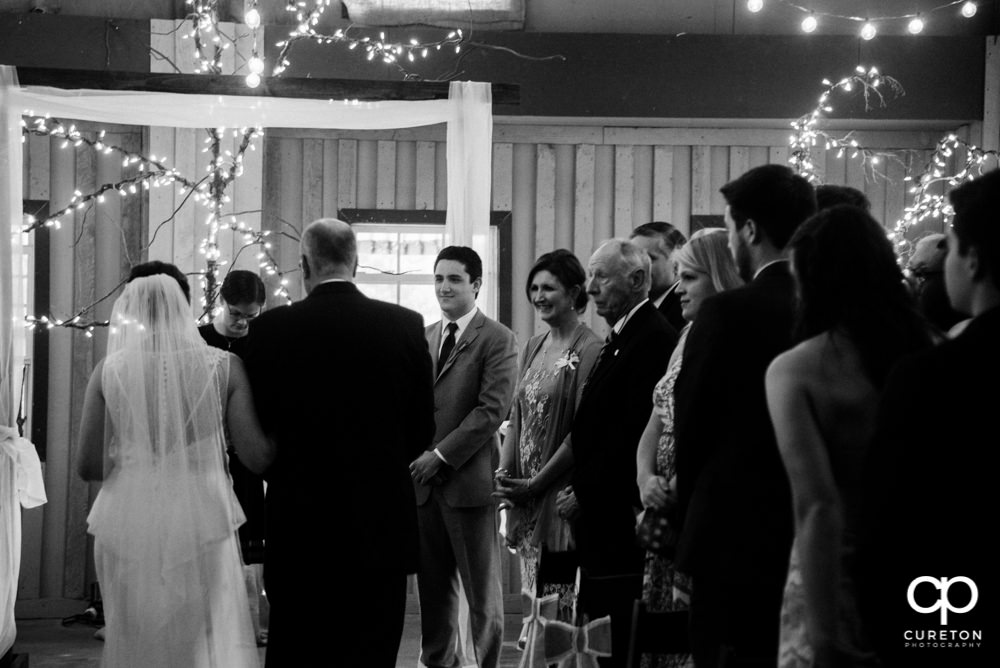 Bride and father walking down the aisle at the indoor wedding at Greenbrier Farms.