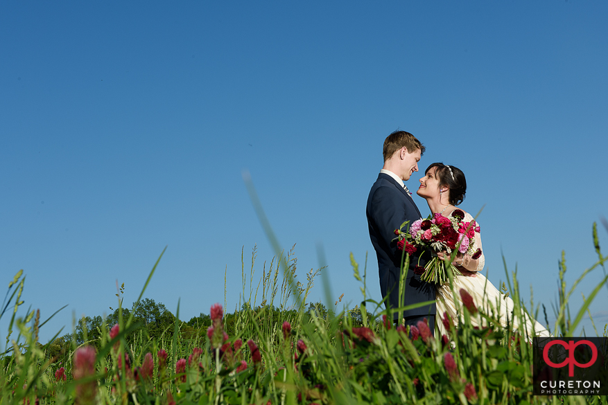 Bride and groom standing in a patch of clover at a rustic farm wedding.