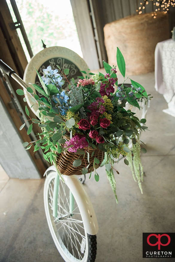 Awesome vintage bicycle adorned with flowers at a rustic farm wedding.
