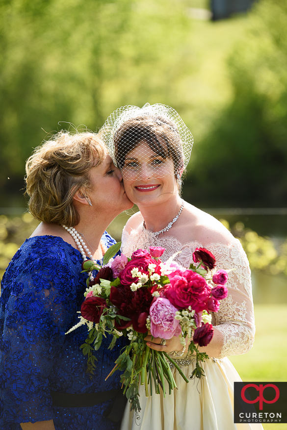 Bride's mom kissing her daughter.