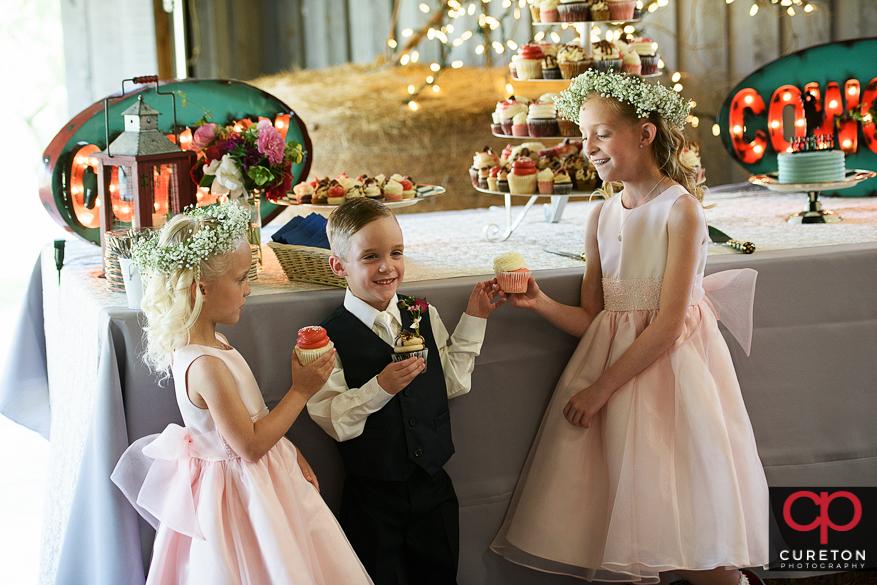 Flower girls and ring bearer sharing a cupcake.