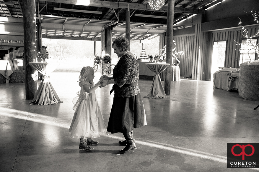 Bride's mom dancing with a flower girl.
