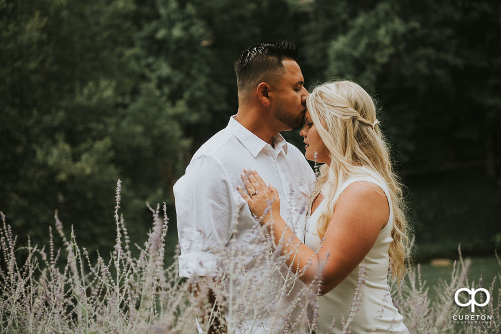 Groom kissing his bride on the forehead during a pre-wedding shoot in downtown Greenville,SC.