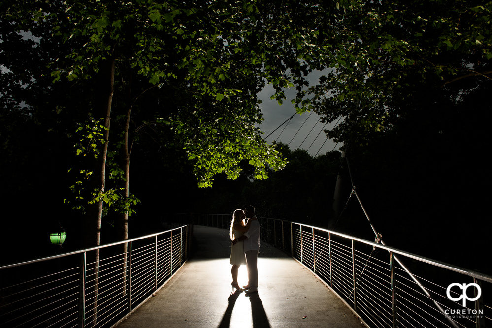 Future bride and groom kissing on Liberty Bridge during an engagement session in downtown Greenville,SC.