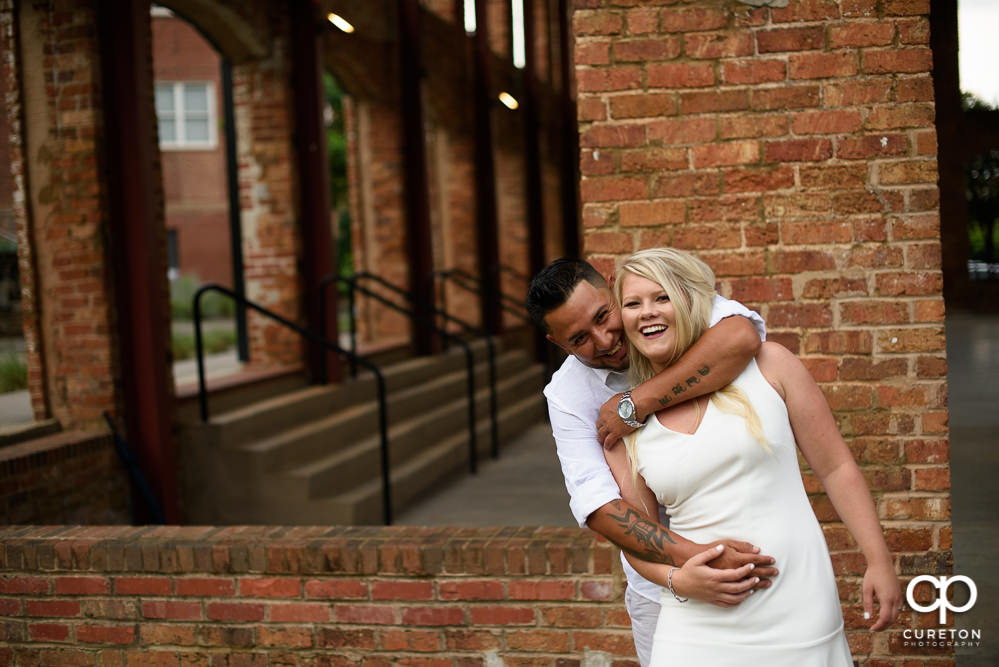 Engaged couple laughing at the Wyche Pavilion.